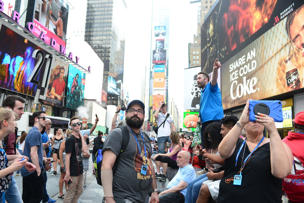 外國政府近幾周來針對美國的旅行警告有明顯增加趨勢。圖為遊客在紐約時報廣場聽導遊解...