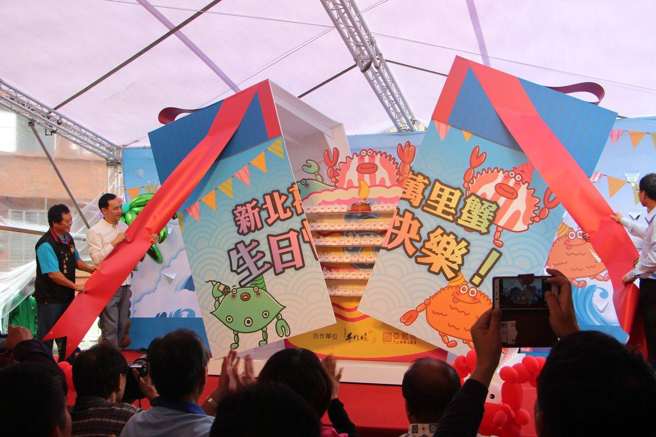 新北市長朱立倫揭開巨無霸蛋糕,為萬里蟹慶生。圖/新北市農業局提供