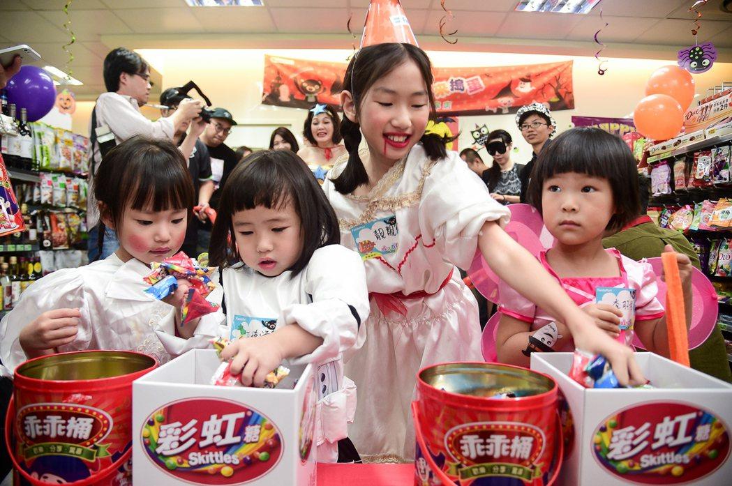 凝凝(左一)和靚靚(右二)與其他小朋友一起抓糖果。圖/全家便利商店提供