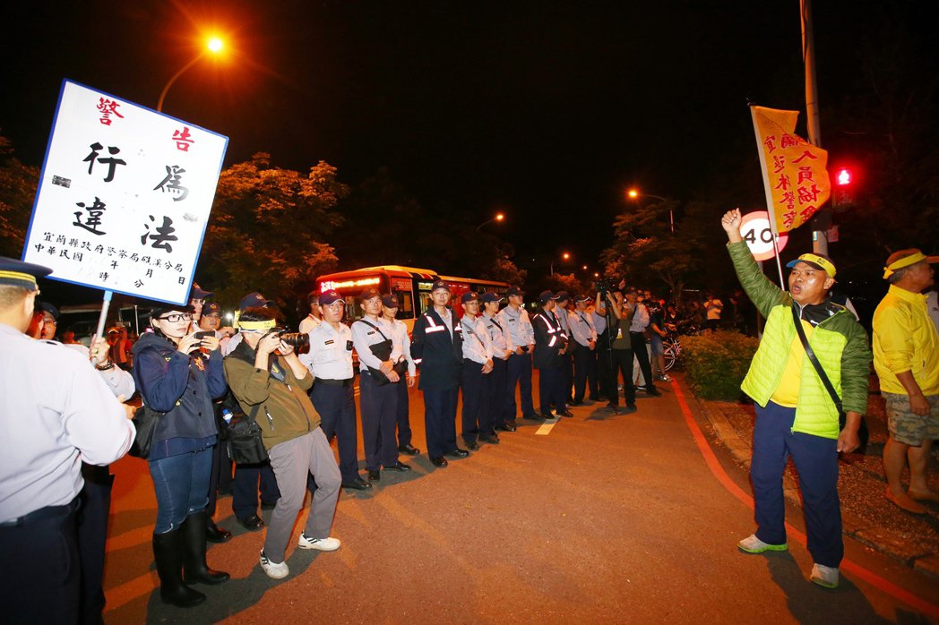 全國運動會今晚在宜蘭開幕,有退警人員在會場外抗議蔡政府,遭警方舉牌警告。記者王騰...