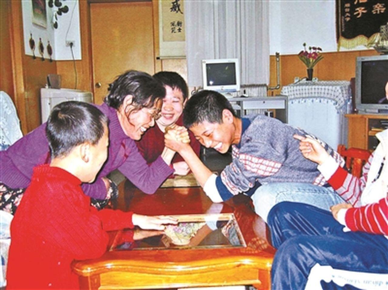 張雨霄在家與孩子們掰手腕。(取材自北京青年報)