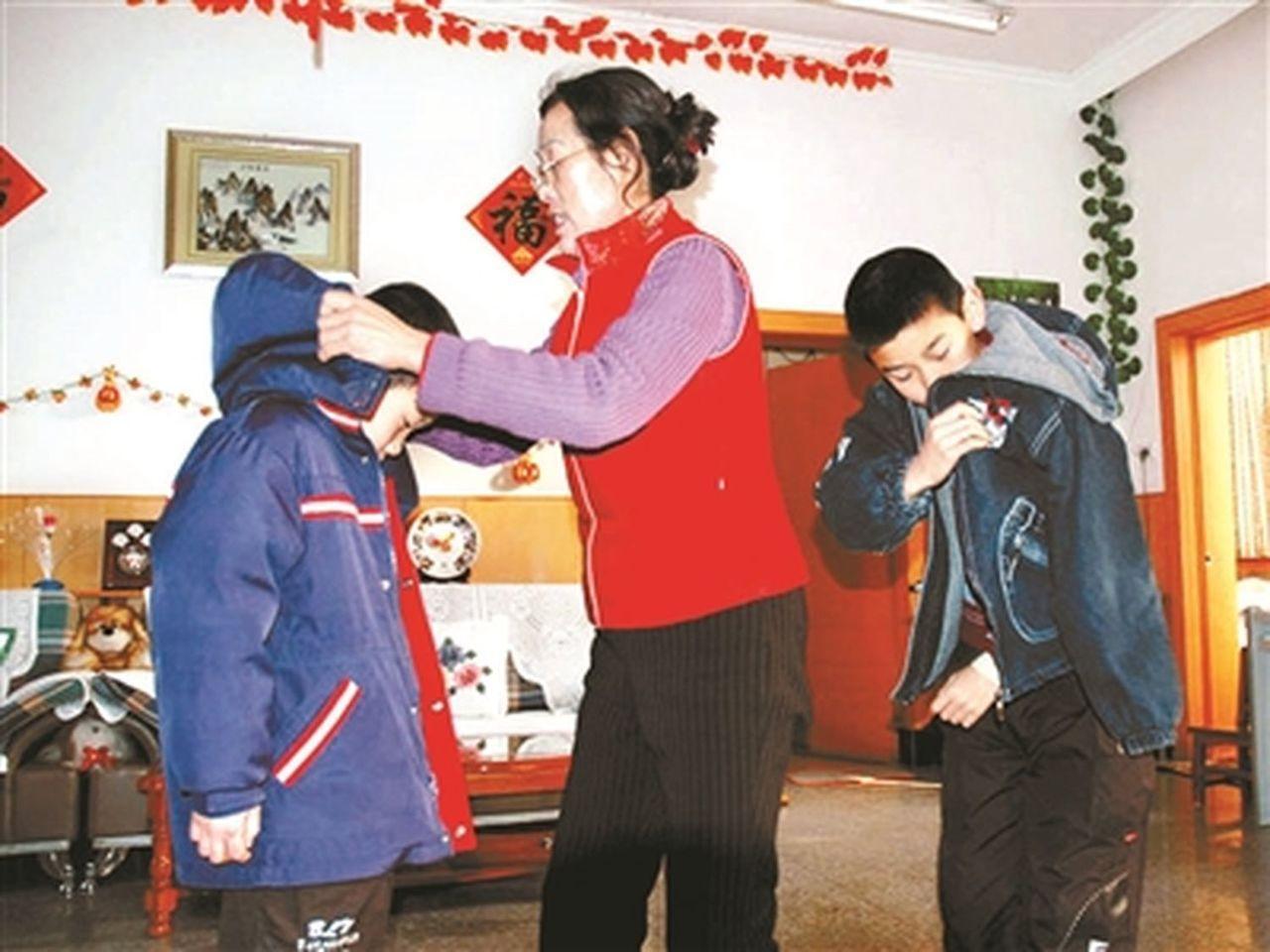 出門前,張雨霄幫兒子穿衣服。(取材自北京青年報)