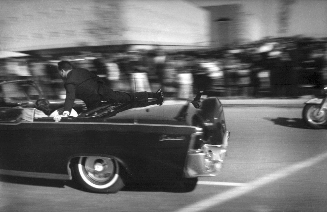 甘迺迪總統被刺後,敞篷車立即加速趕往醫院,特勤人員俯在車上保護總統和第一夫人。(...