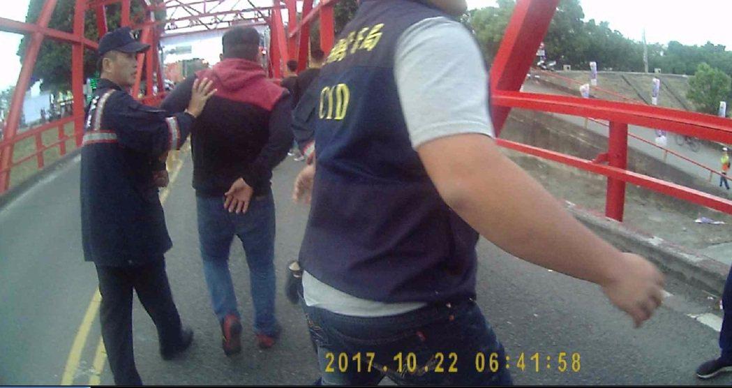 一群從彰化到雲林西螺喝酒的民眾今天在西螺大橋上滋事,被警方強行帶走。記者胡瑋芳/...