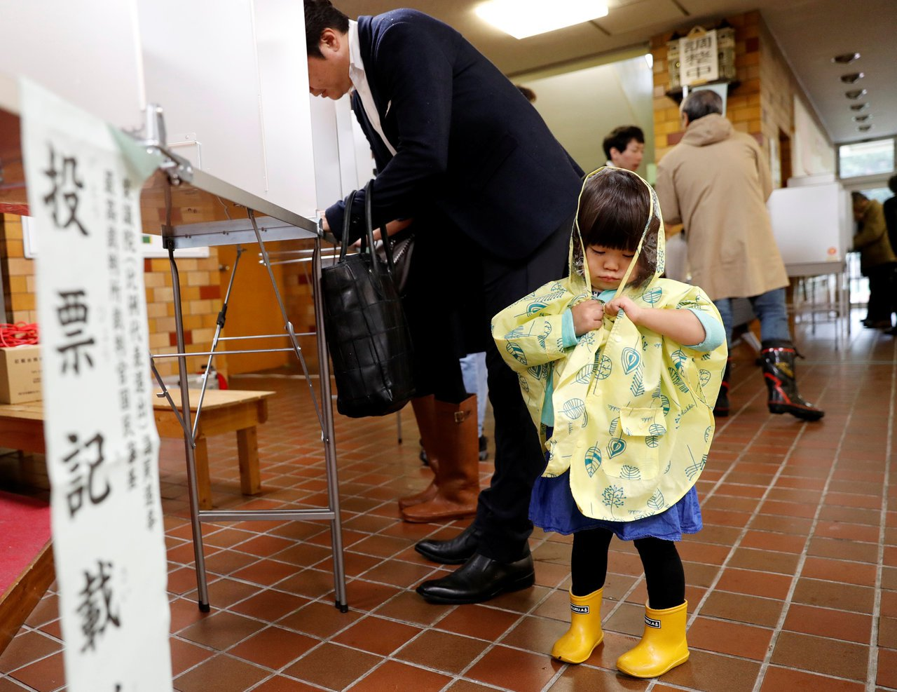 雖然投票日遇到下雨天,一名父親還是帶著女兒來投票。路透