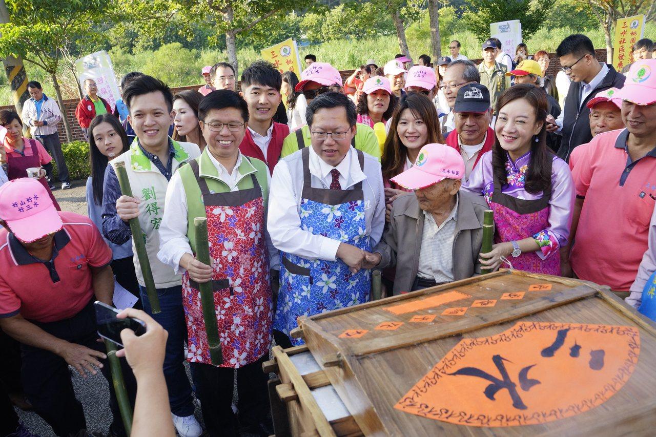 客家局局長蔣絜安(右2起)問阿公陳阿回市長做的客家菜包及格嗎,老人家點頭說可以,...