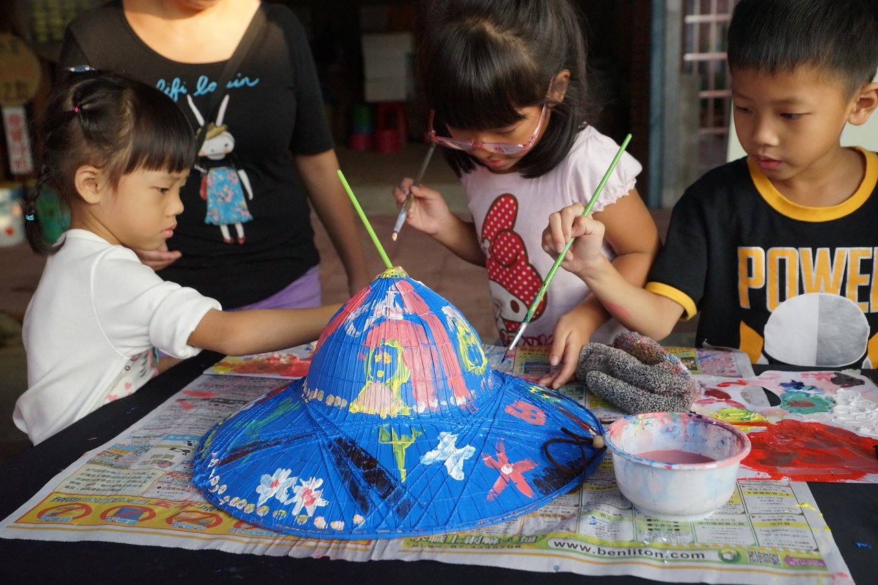 小朋友學客家菜包也忙著彩繪斗笠。圖/桃園市客家事務局提供