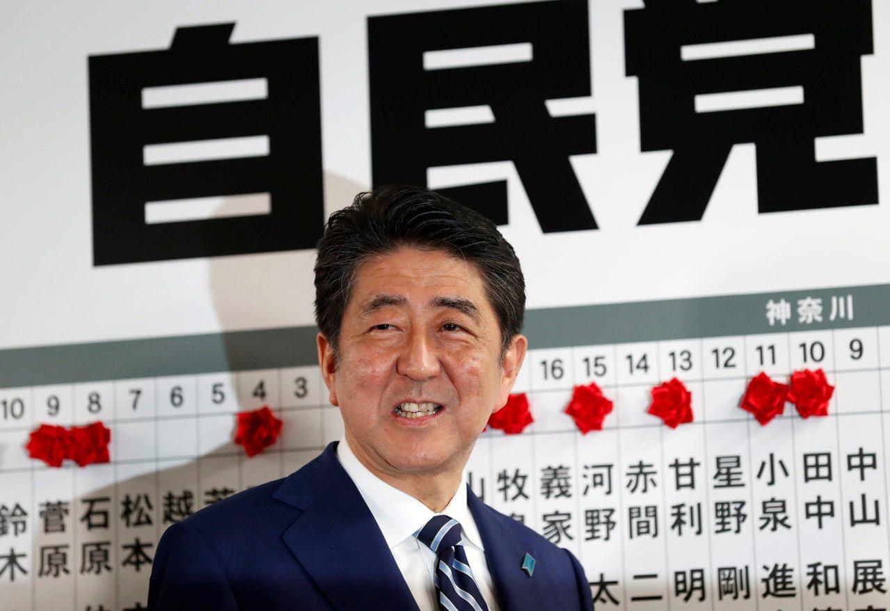 將玫瑰花飾置於預期將當選的議員姓名上方後,日相安倍晉三露出愉快笑容。路透