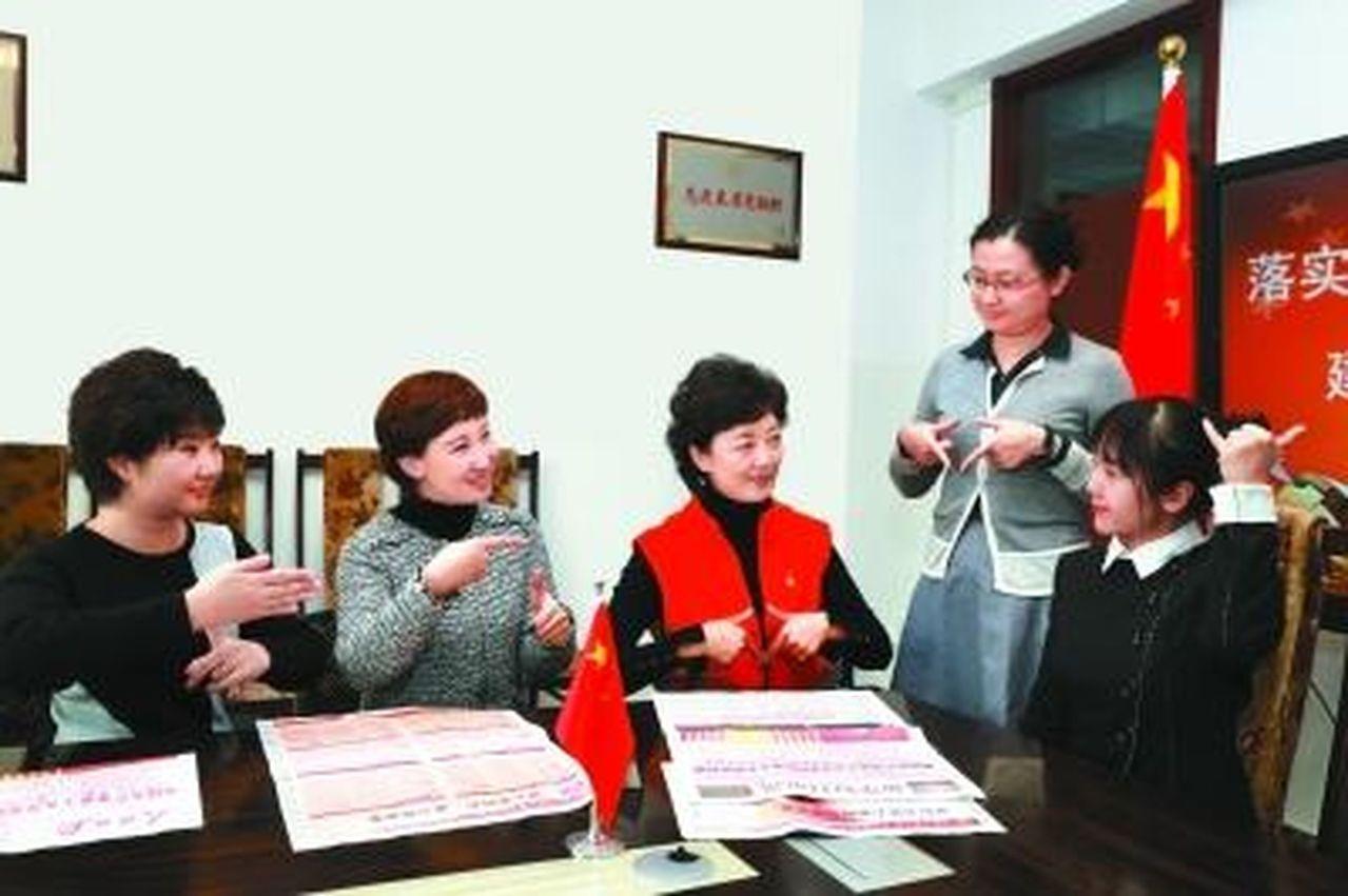 19大報告手語翻譯周曄(左三)和老師們共同練習「高舉中國特色社會主義旗幟,堅持走...