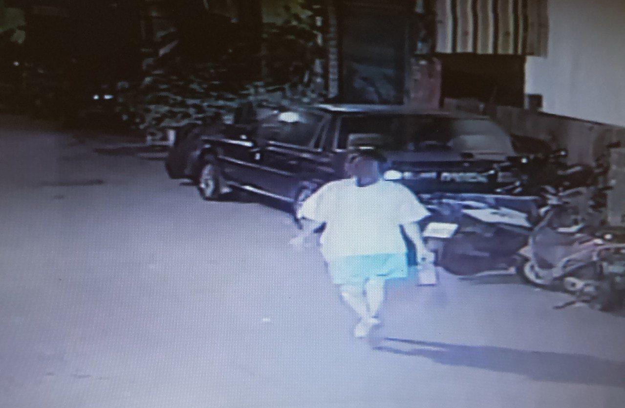 邱姓女子提著不明液體找同事的機車動手腳,經巷內監錄系統錄下。記者林保光/翻攝