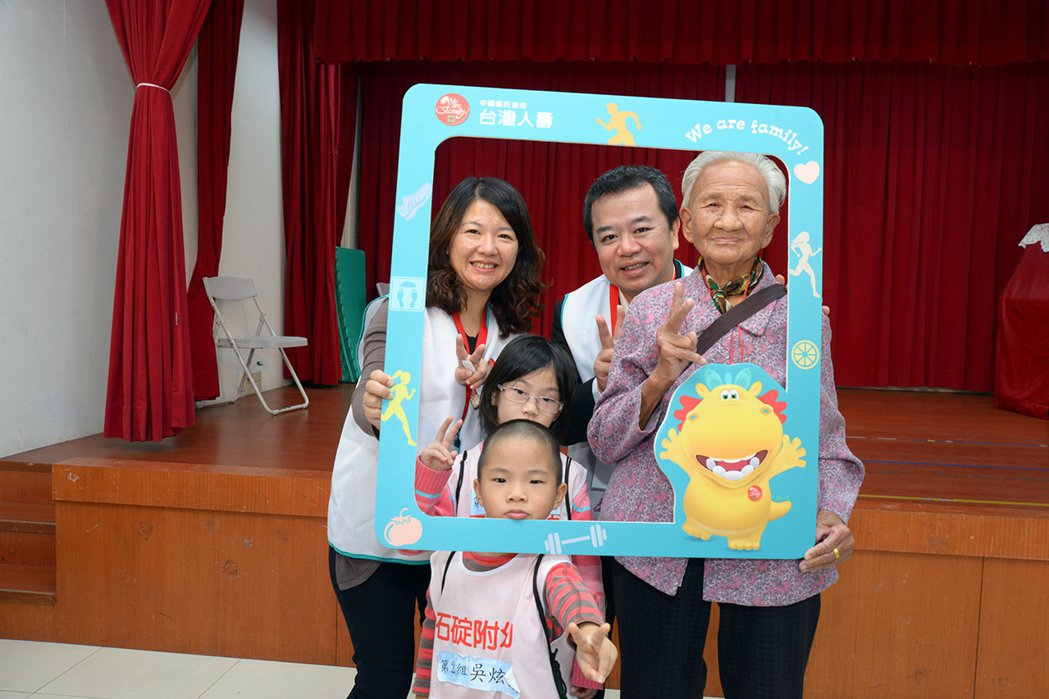 台灣人壽資深副總卓長興(右二)、台灣人壽志工同仁,與現場組成的「一老兩小新家庭」...