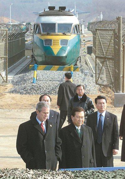 二○○二年,時任美國總統的布希(左)在南韓總統金大中(中)陪同下參觀非軍事區。 ...
