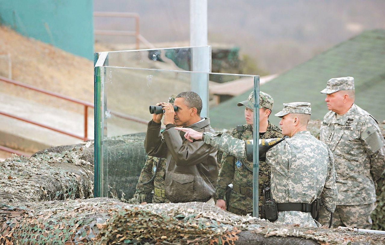 二○一二年,時任美國總統的歐巴馬(左)參訪兩韓邊界非軍事區,拿望遠鏡眺望北韓。 ...
