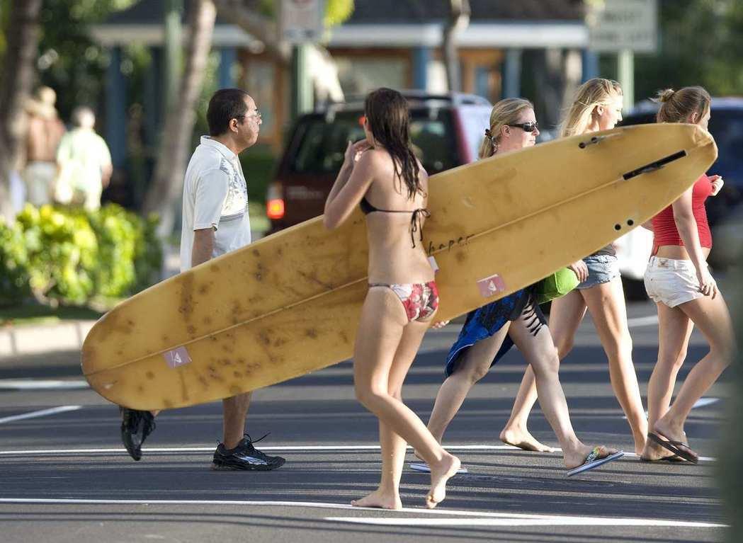 檀香山遊人如織,一名衝浪女孩正在過馬路。 路透