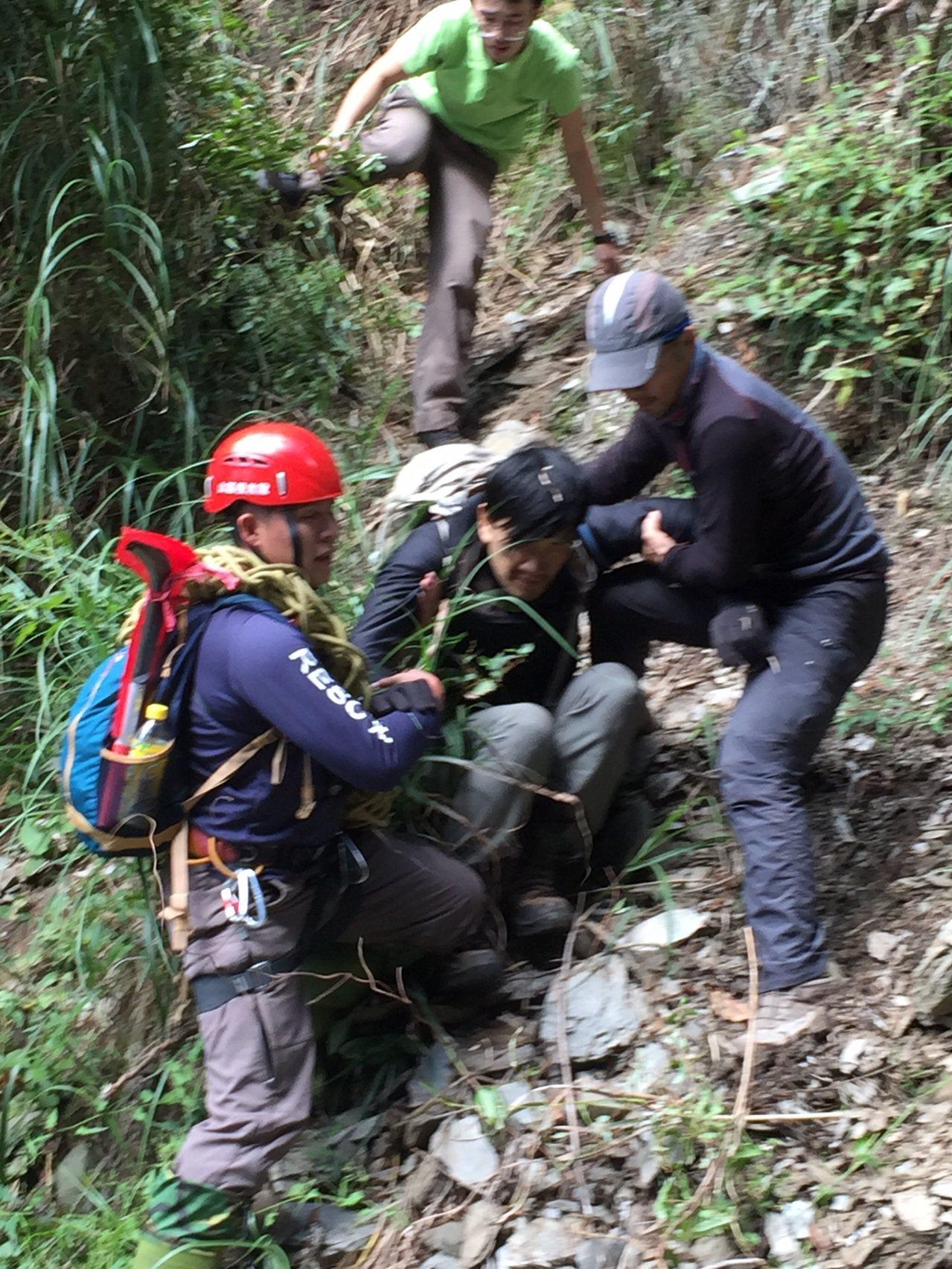 黃致遠(中)受困山區12天,今天獲救由搜救人員攙扶下山。圖/南投縣消防局提供