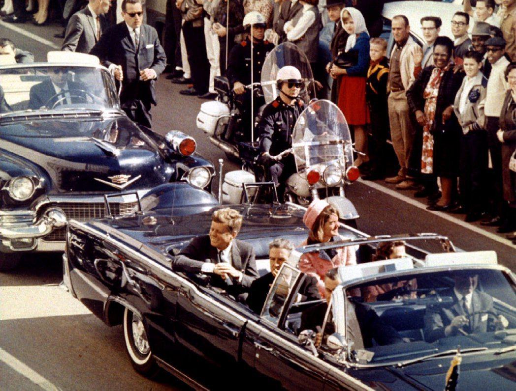 甘迺迪遇刺前,與夫人賈桂琳一起坐在車內,接受達拉斯居民夾道歡迎。 (路透)