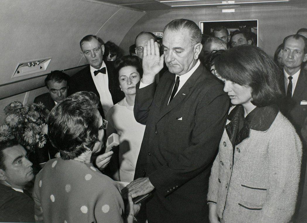 副總統詹森於甘迺迪遇刺後,於空軍一號總統座機內宣誓就任總統,旁為甘迺迪遺孀第一夫...
