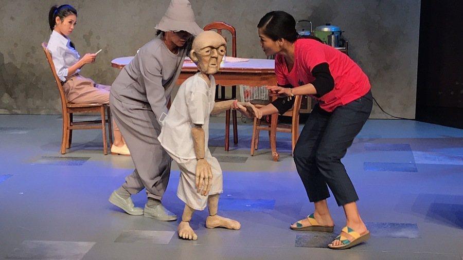 舞台上老伯伯戲偶一舉一動都得靠演員攙扶,將年長者孱弱的形象、外籍看護的細心照顧刻...