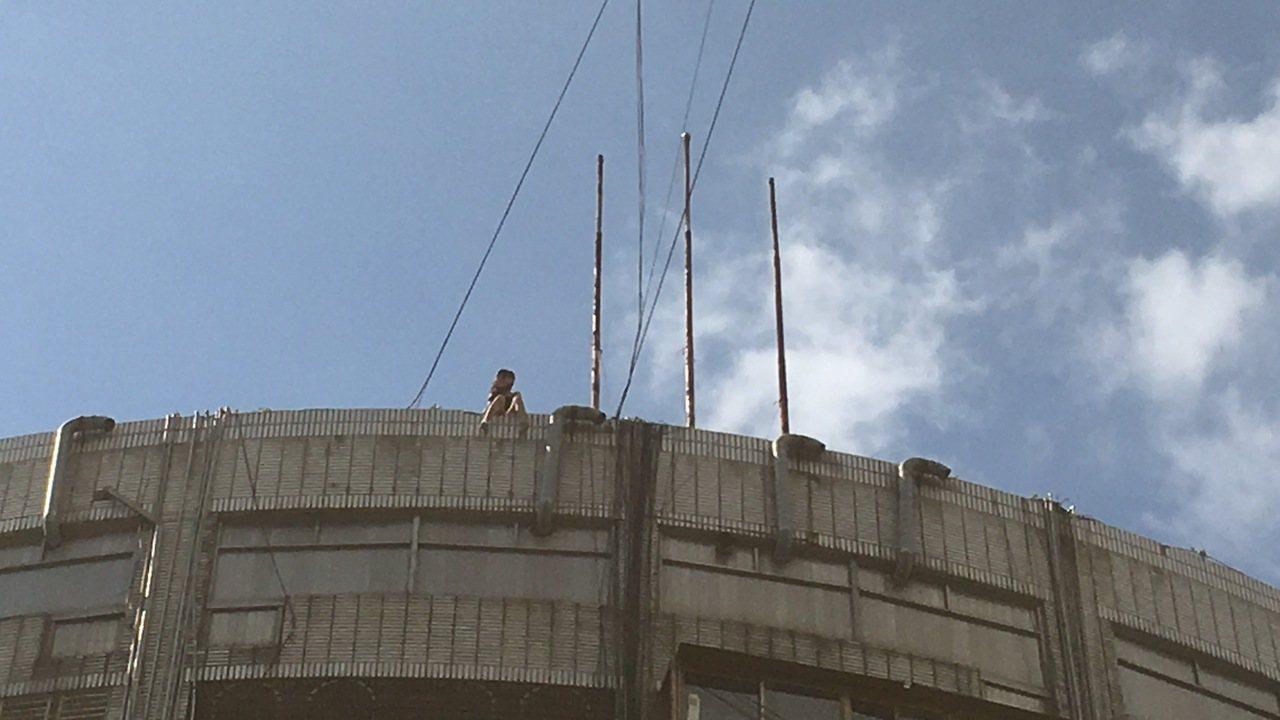 佟女坐在樓頂狀似要輕生。記者李承穎/攝影