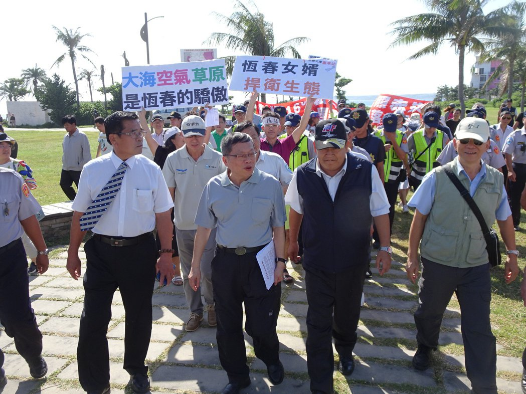 營建署長許文龍(中)南下墾丁現勘,2個訴求不同的陳抗團體在後方拉布條、高聲表達訴...