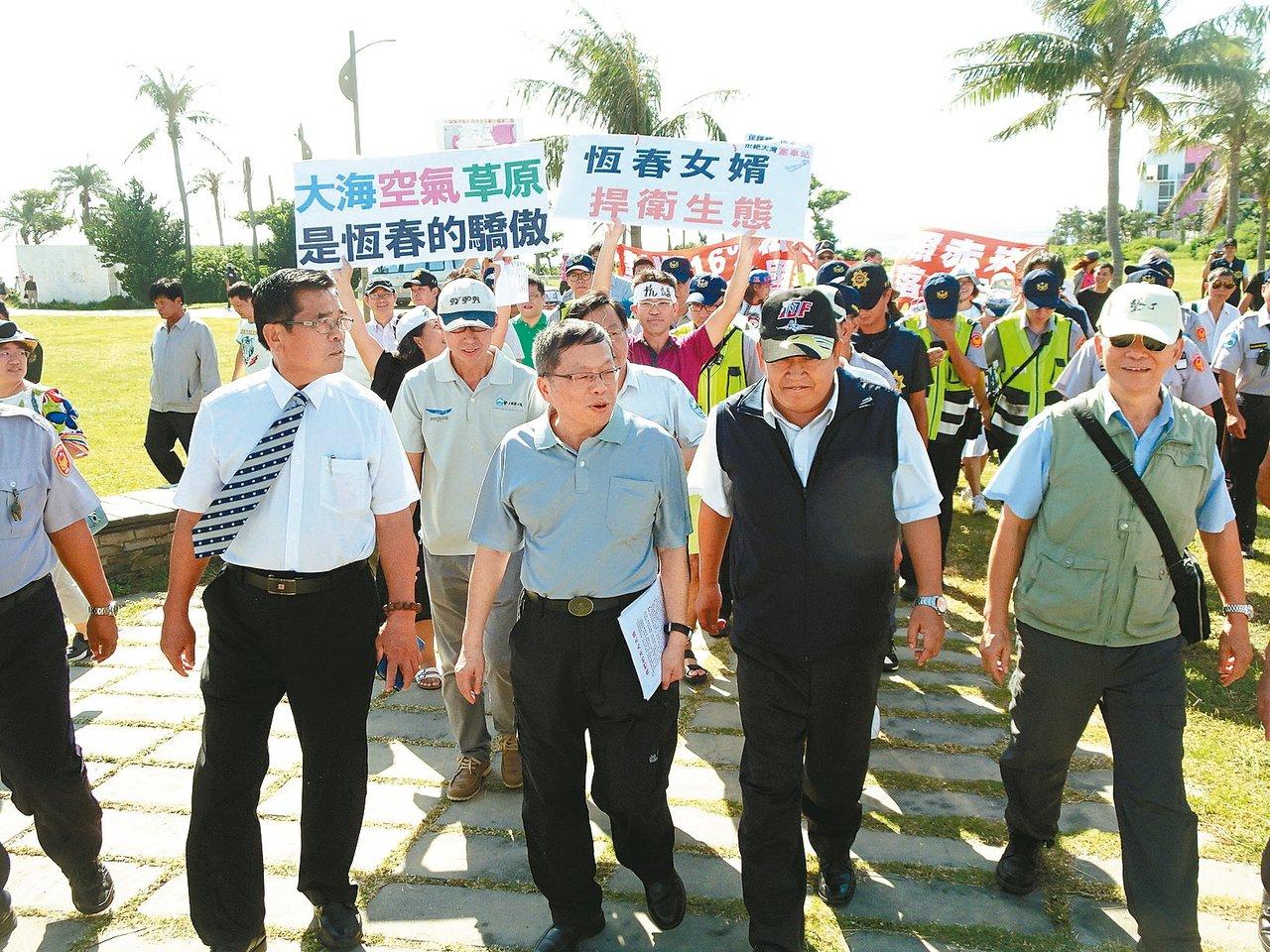 營建署長許文龍(中)南下墾丁現勘,兩個訴求不同的陳抗團體在後方拉布條、高聲表達訴...