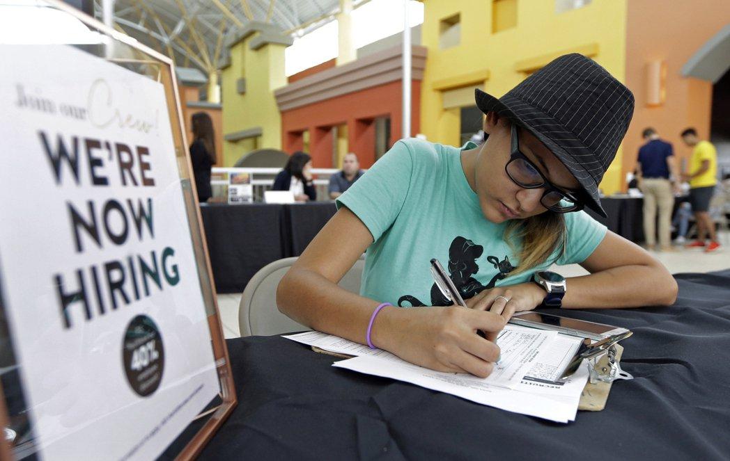一名年輕人在就業博覽會填資料。美聯社