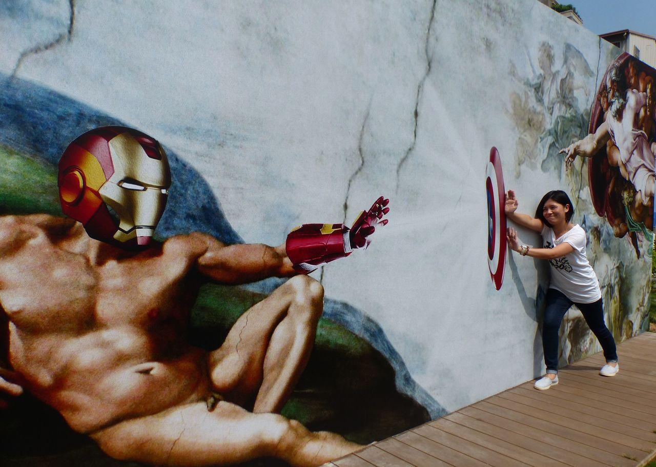 米開朗基羅《創世紀》裡的亞當怎麼變成鋼鐵人?吸引遊客與KUSO名畫拍照打卡。記者...