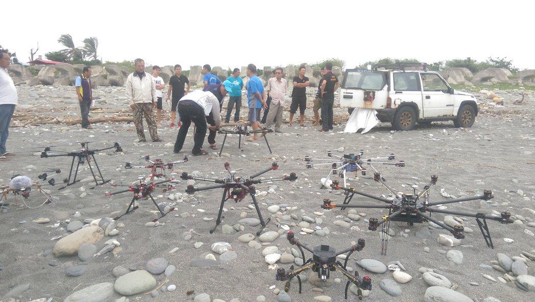 台東有釣客與科技救難協會成員聚集海邊,將數架空拍機擺在沙灘上,針對無人機使用限制...