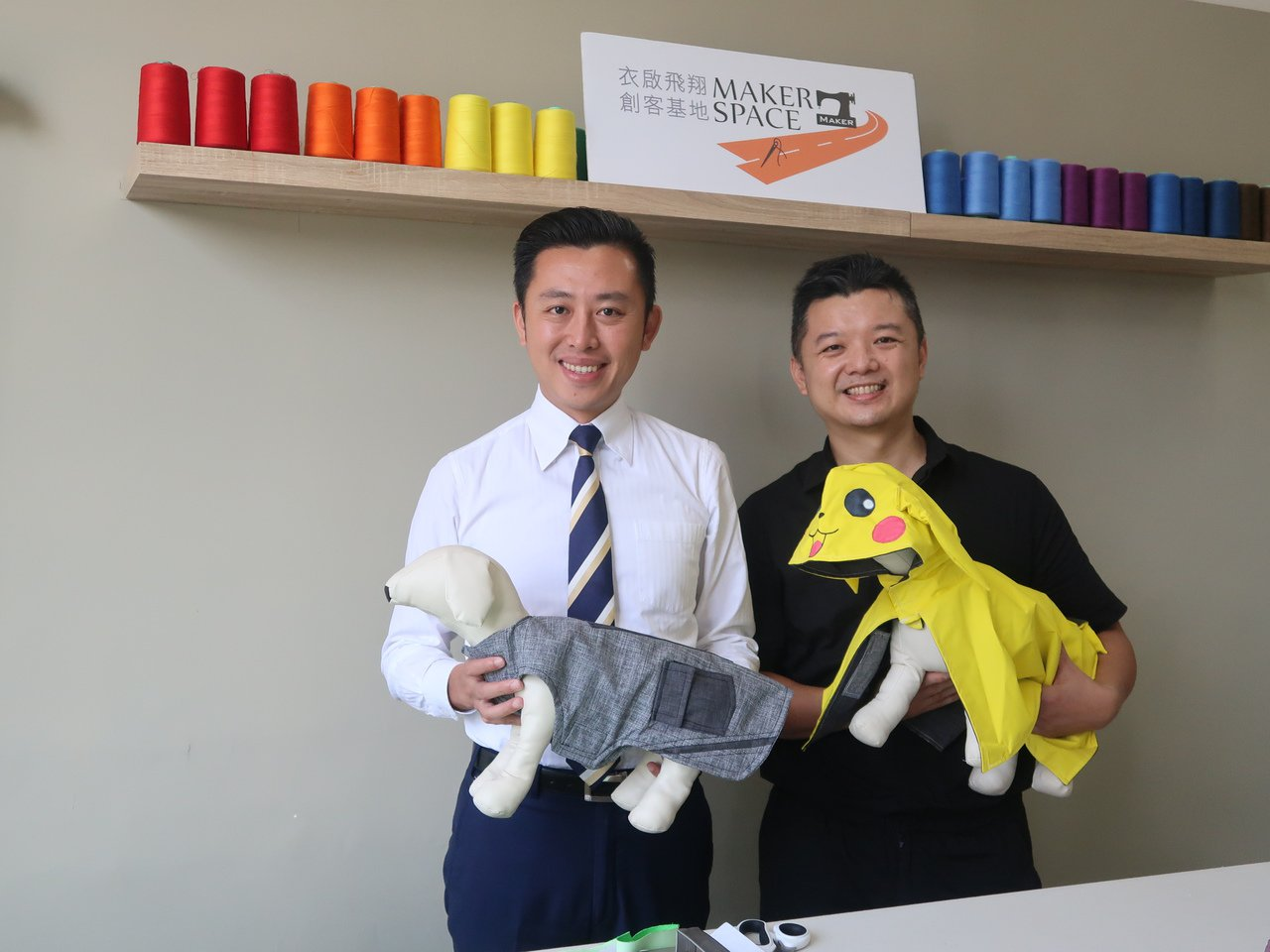 新竹市長林智堅(左)稱讚黃饒鋒(右)設計的「寵物雨衣」美觀又實用。 記者林家琛/...