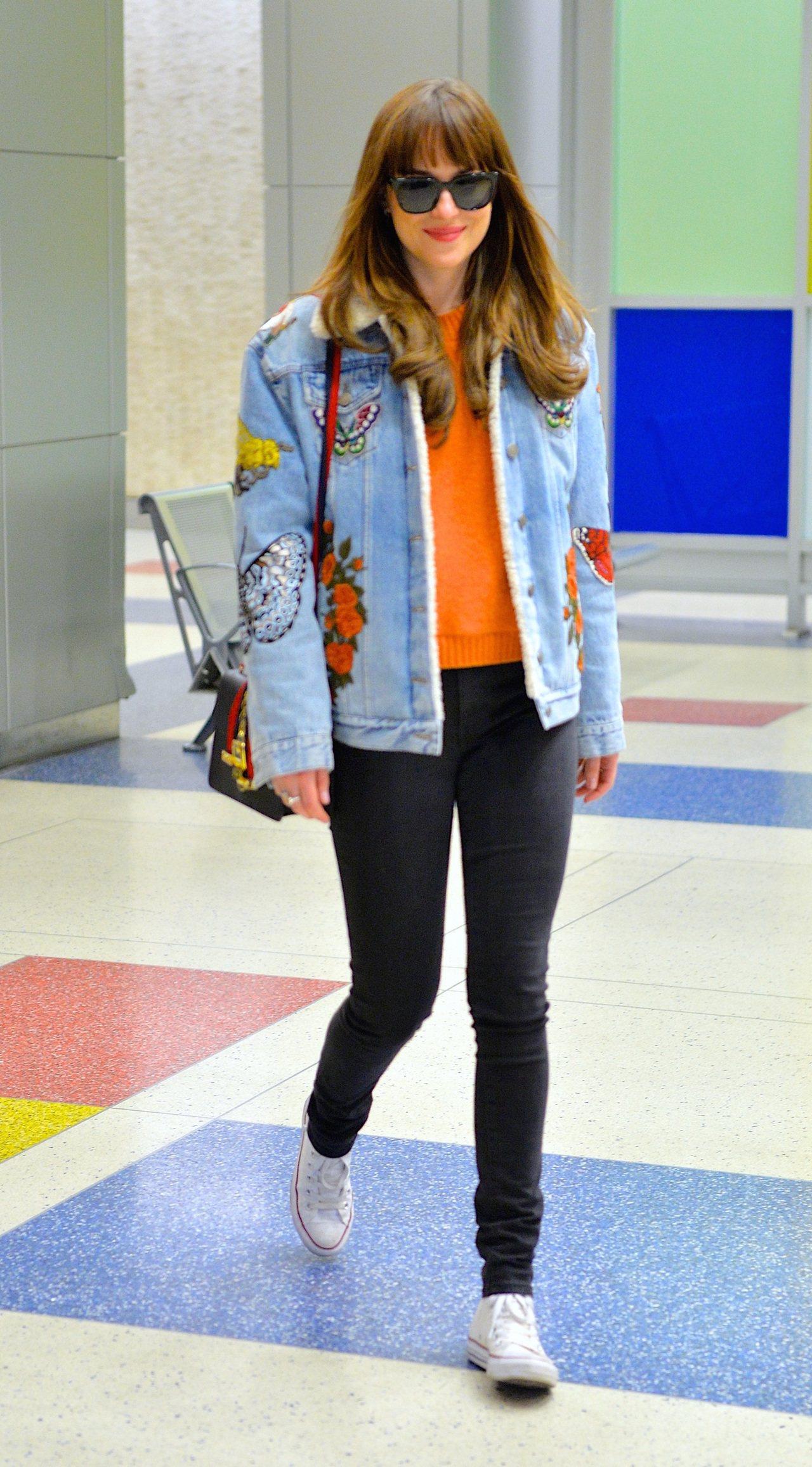 Dakota Johnson以黑色包搭配刺繡牛仔夾克。圖/古馳提供