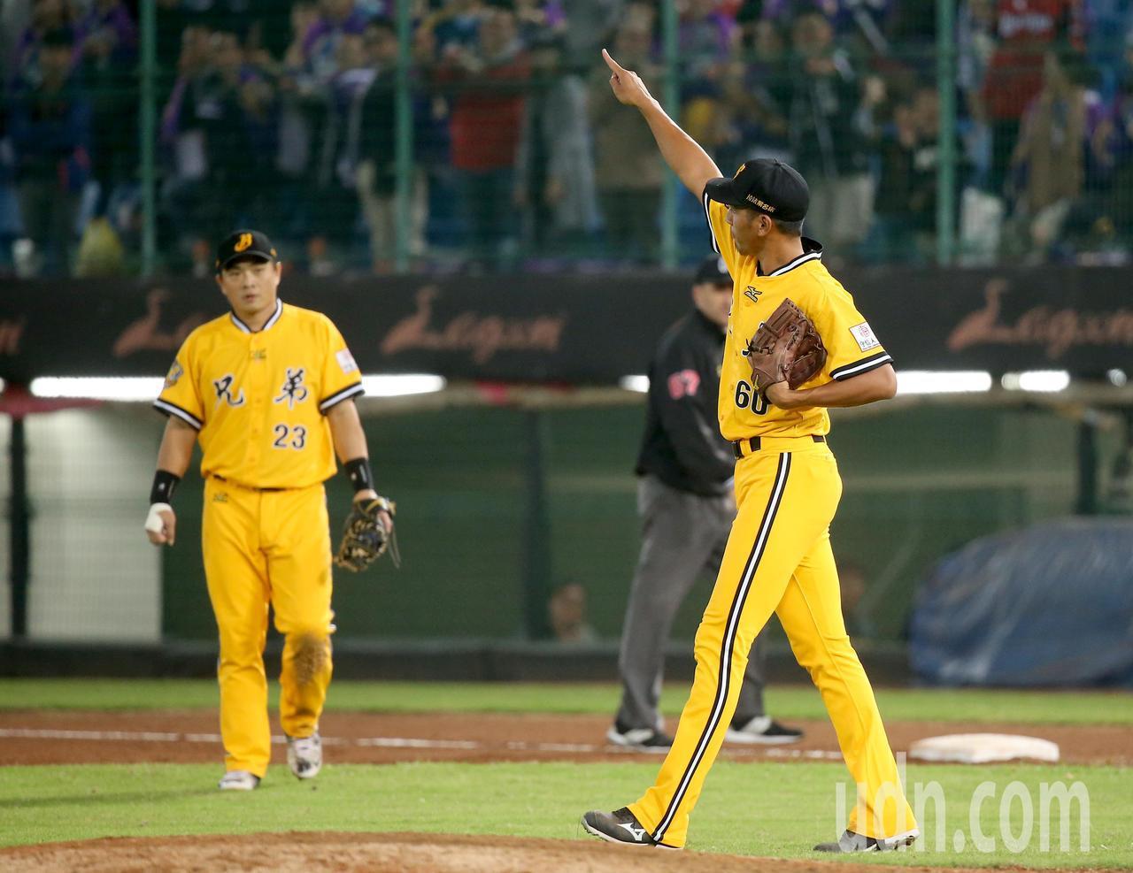 中華職棒總冠軍賽首戰,中信兄弟後援投手王鴻程(右)在抓下最後一個出局數後,興奮地...