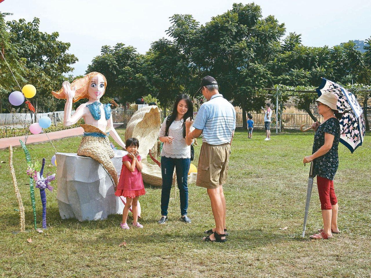 工藝稻草文化節在草屯植物公園登場,大小朋友與稻草藝術合影。 記者賴香珊/攝影