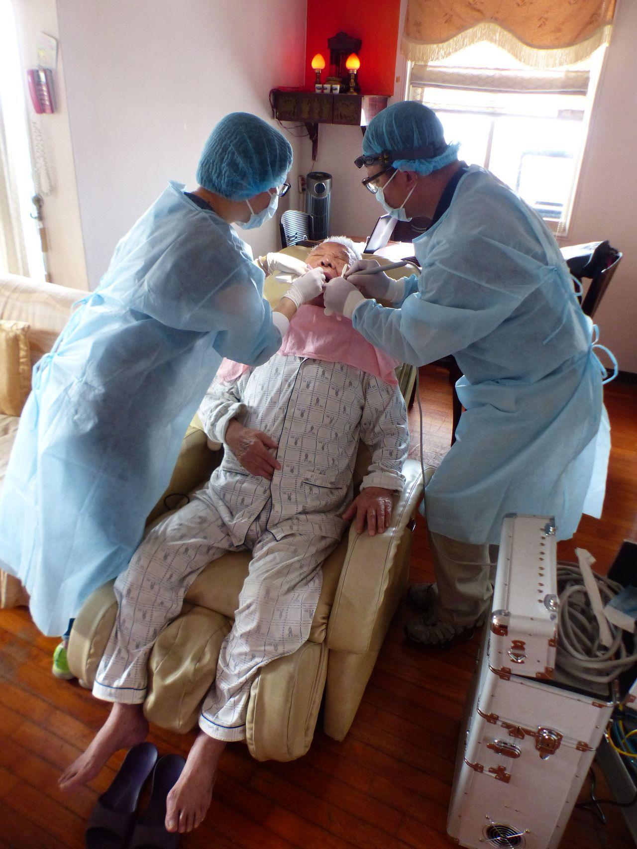 牙醫羅界山(右)與同是牙醫的妻子(左)在高姓老兵家中為他洗牙、診治。記者趙容萱/...
