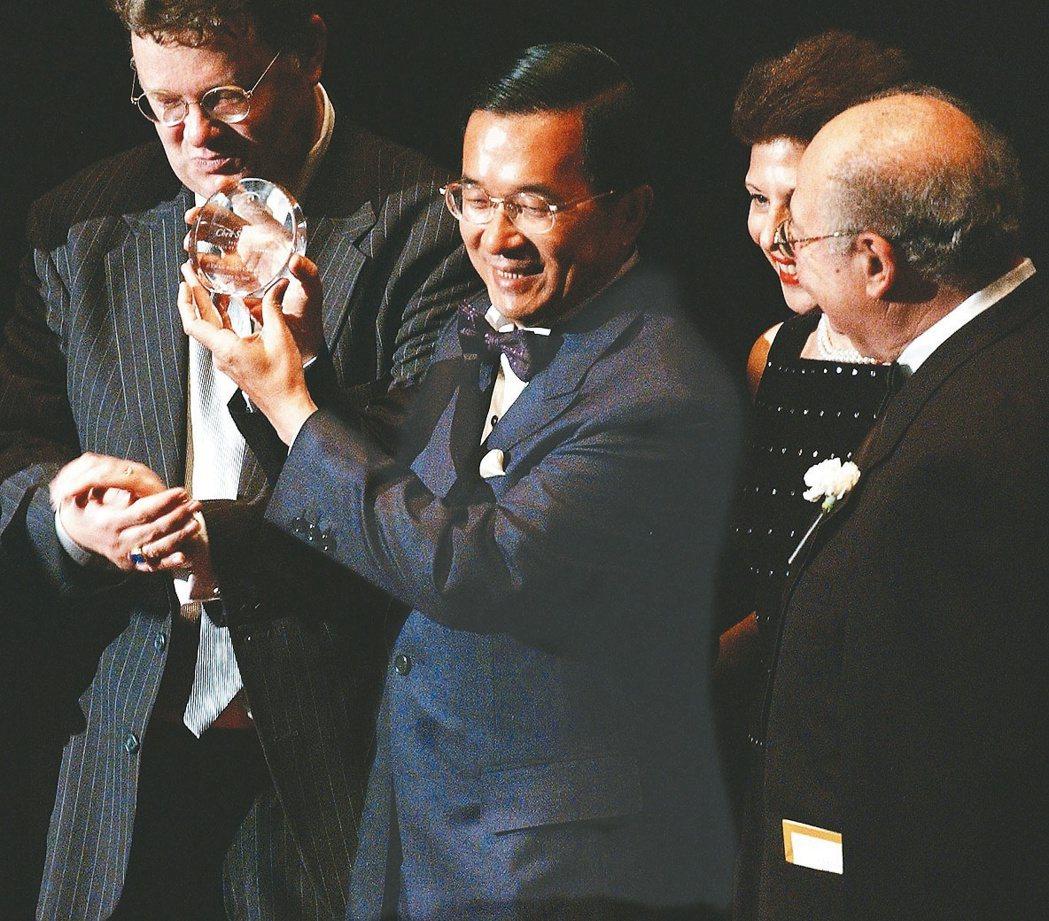 前總統陳水扁在2003年出訪巴拿馬期間,過境美國接受國際人權聯盟頒獎後,舉起獎座...