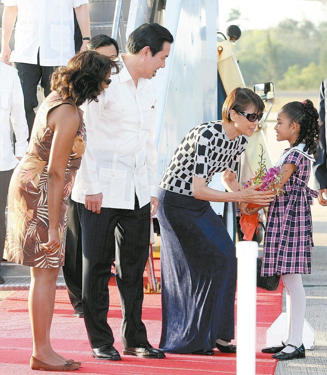 前總統馬英九(左)2009年久睦之旅飛抵貝里斯,與夫人周美青(中)下機後接受獻花...