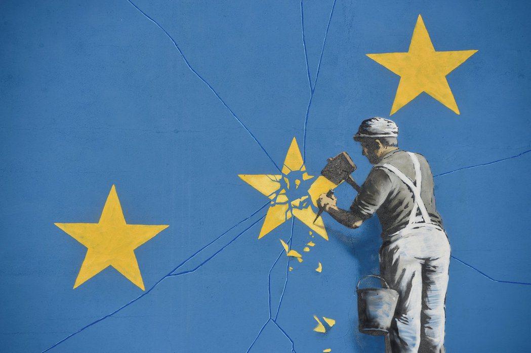 英國匿名塗鴉藝術家Banksy在英國脫歐公投後隔一年,在靠近多佛港口處的一棟建築...