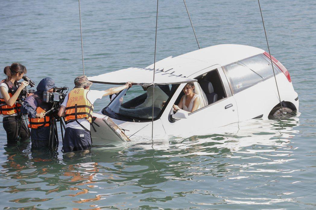 孫燕姿半沉於大海中,身穿白紗坐在車裡。圖/環球提供