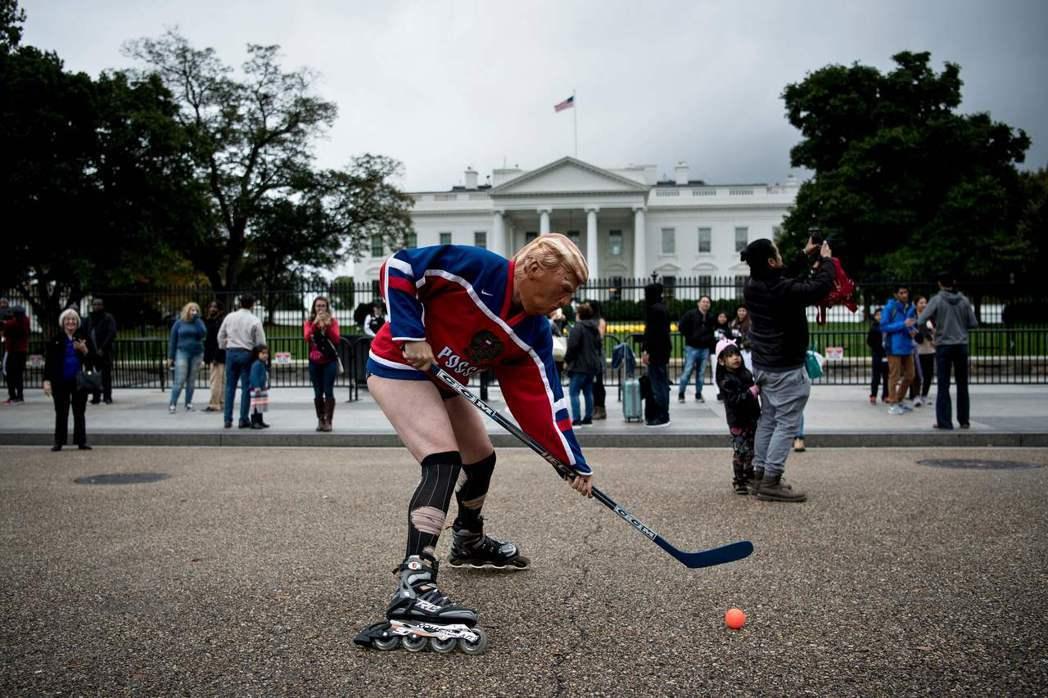 一名男子廿九日戴著美國總統川普面具,穿著俄羅斯國家男子冰球隊球衣在白宮前打球,暗...