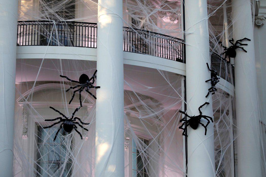 美國白宮在30日變成「鬼屋」,外牆佈滿蜘蛛網並掛上假蜘蛛等萬聖節裝飾。 (路透)