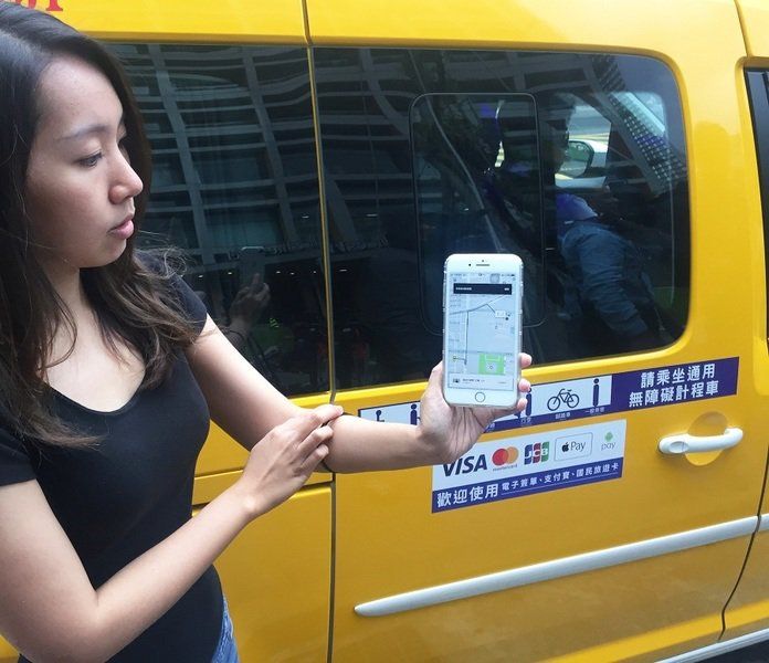 圖為工作人員正在示範使用uberTAXI的APP,現場叫車相當便利。(photo...