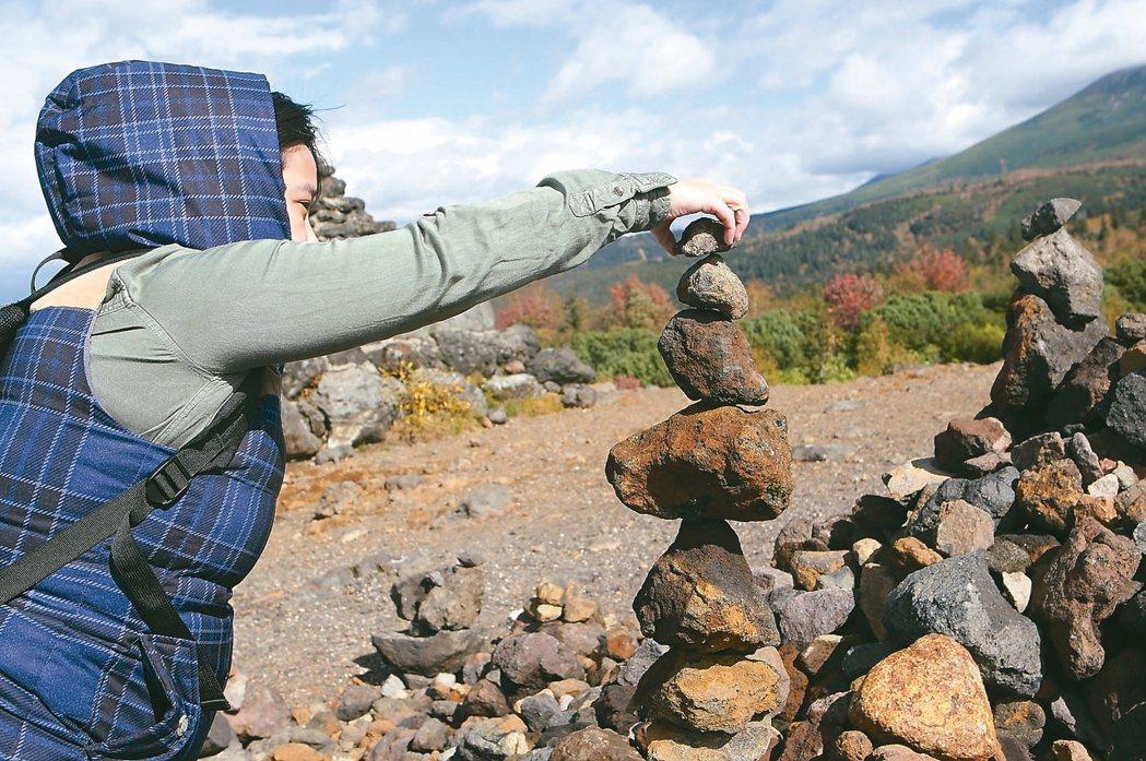在十勝岳堆砌石塔祈願,是許多登山客必做之舉。 記者陳睿中/攝影