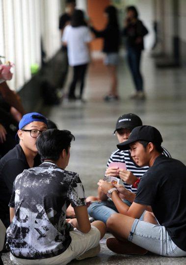 高中英語聽力測驗考生在試場外三五好友聚在一起玩撲克牌放鬆考試心情。本報資料照/記...