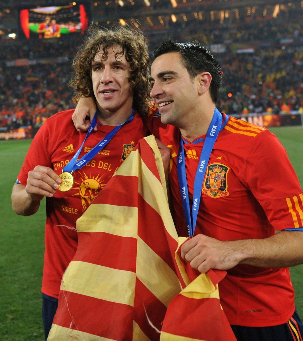 2010年世界杯足球賽決賽對陣荷蘭,西班牙奪冠後,球員普約爾(左)和哈維手持加泰...