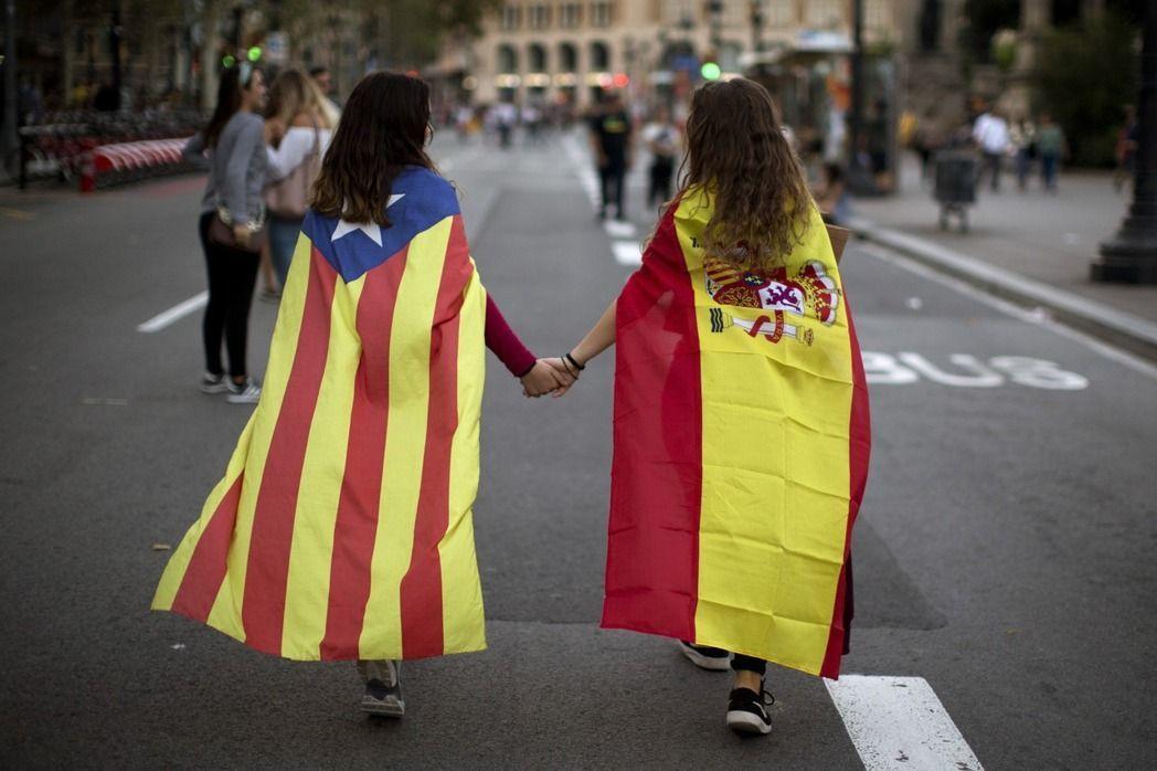 披著西班牙國旗(右)的少女,和另一名披著加泰隆尼亞獨立運動旗幟的少女,手牽手走在...