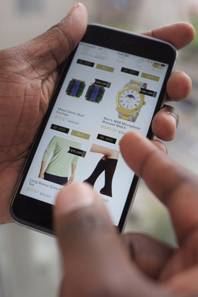 亞馬遜改變消費者購物習慣,讓折扣券走入末日。圖為消費者用手機查詢貨品折扣。 (美...
