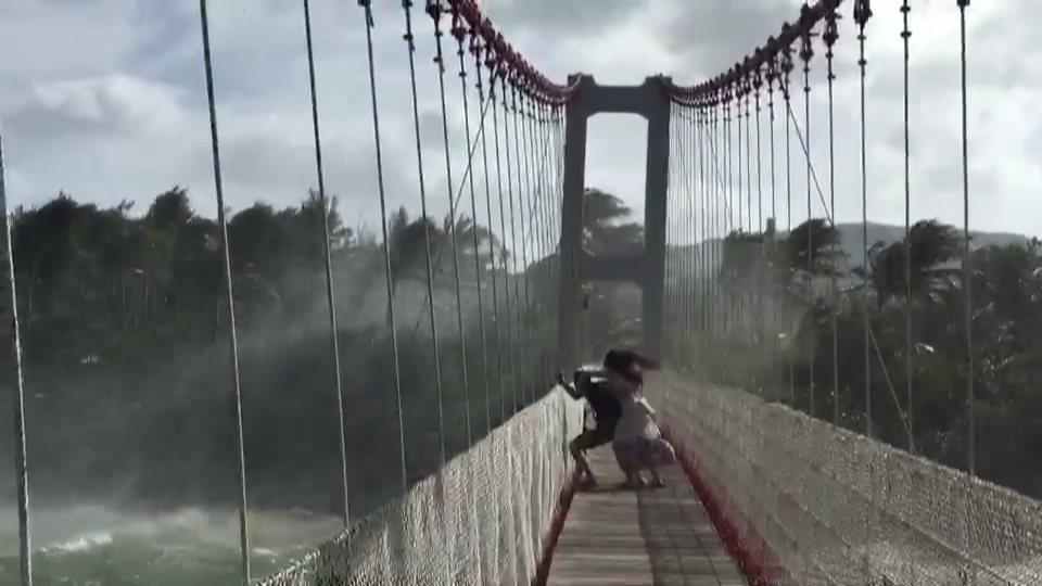 一對情侶上到屏東滿州鄉港口吊橋,被強陣風吹到緊抓欄桿不放,因搖晃劇烈嚇得尖叫。記者潘欣中/翻攝