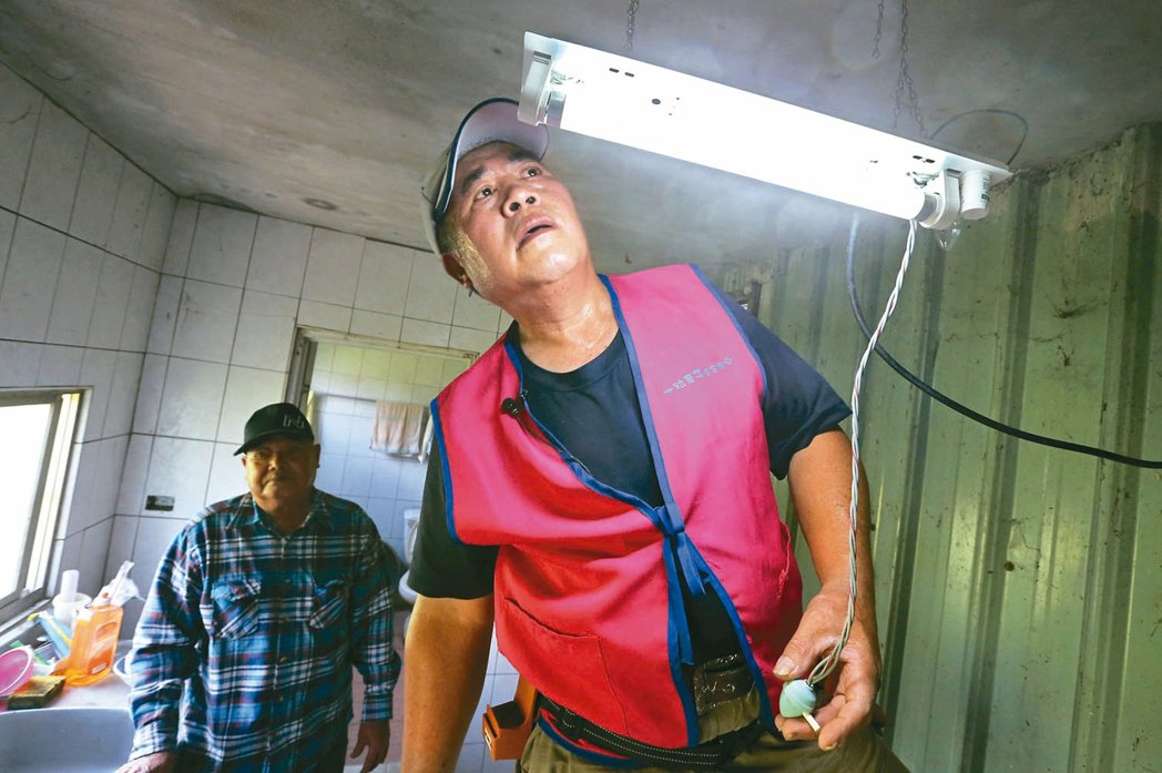 便利屋服務員幫老人修電燈。 記者胡經周/攝影
