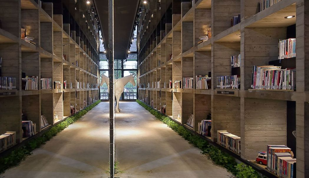 樂樂書屋的書架用水泥鑄造,粗獷材質與收藏的書籍產生對比趣味。 圖/樂樂書屋提供