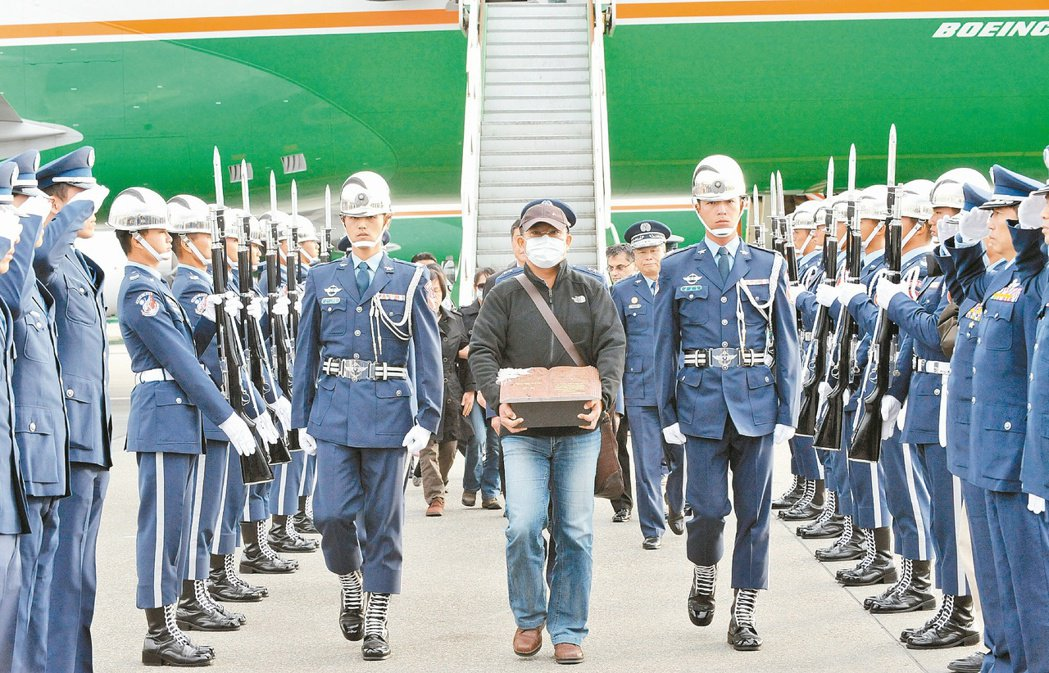 空軍飛官王同義骨灰返回台灣時,由胞兄手捧忠靈罐步下飛機,接受隆重軍禮迎靈。圖/桃...