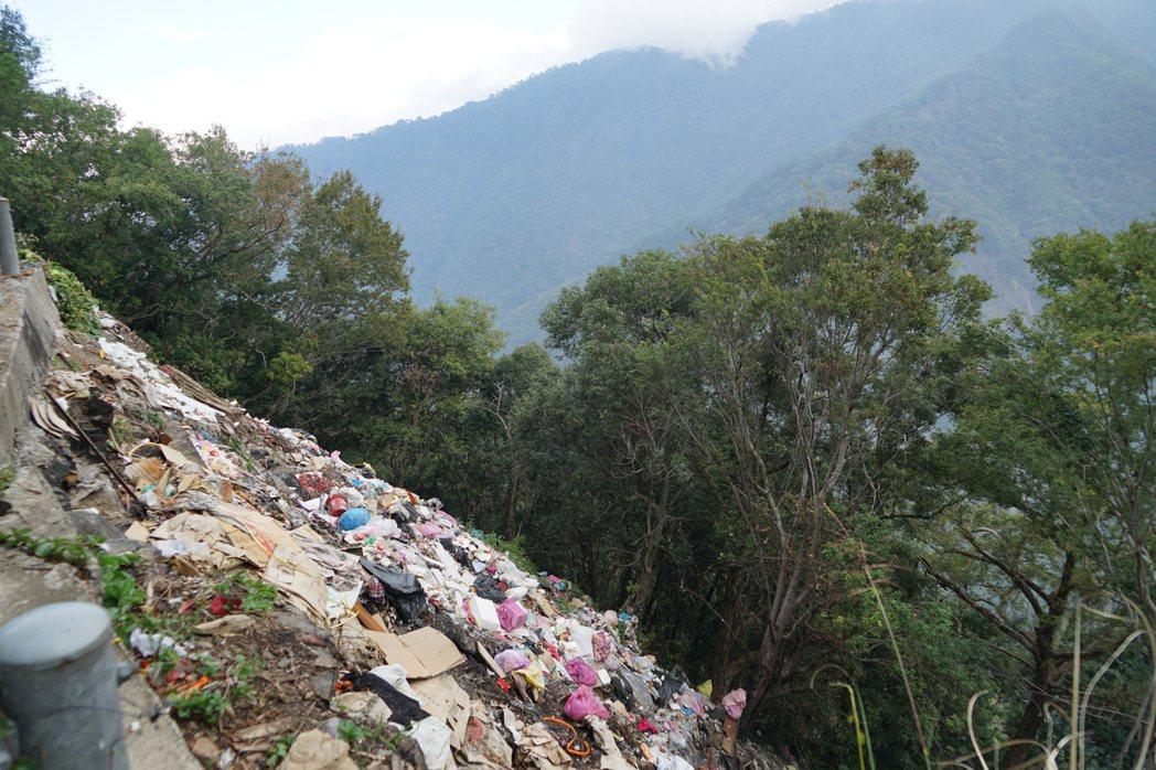 垃圾瀑布和對面的美麗高山形成強烈對比。記者陳妍霖/攝影